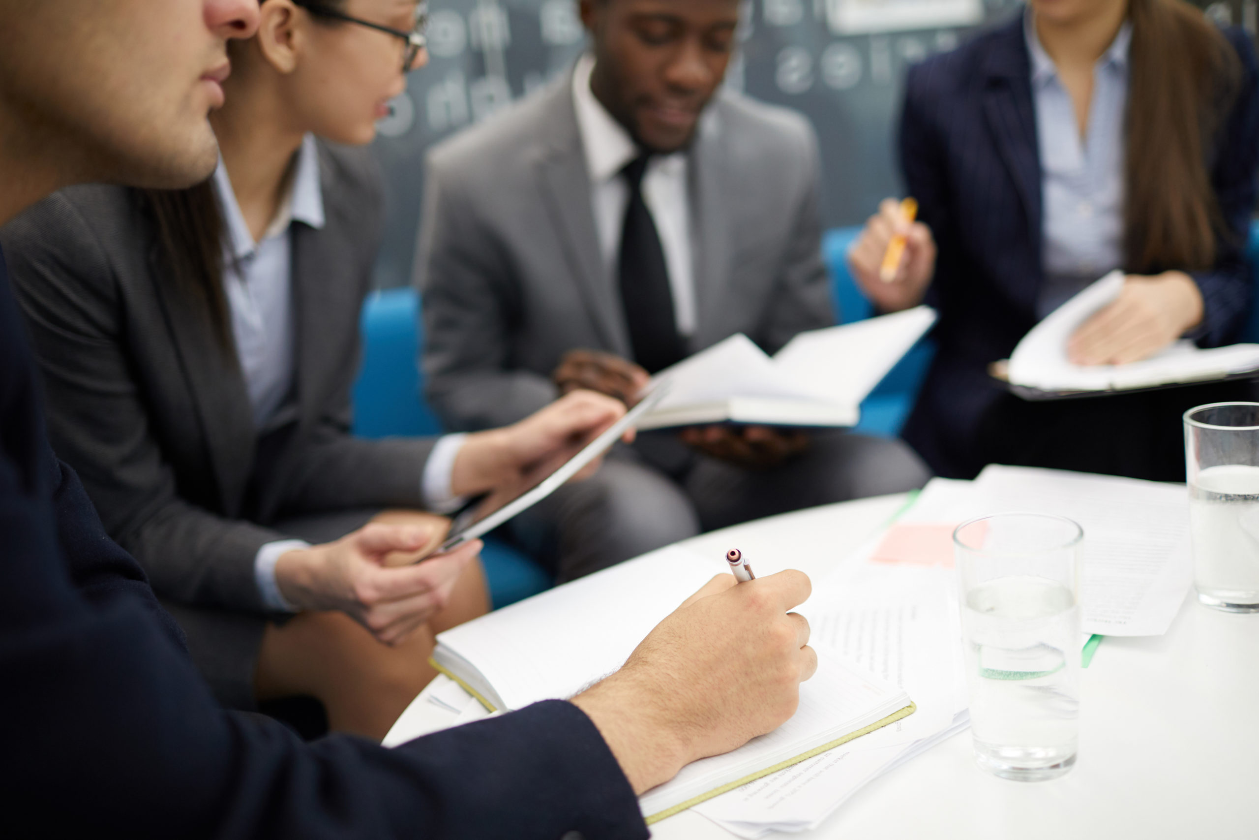 Cropped image of business people writing uring meeting in office, copy space